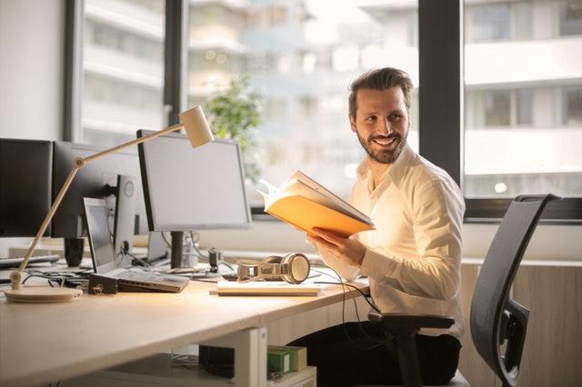 Usmiaty muž za kancelárskym stolom.jpg