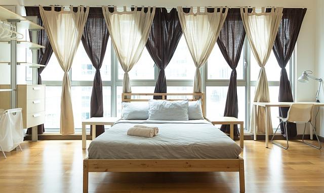 Veľká drevená posteľ s matracom uprostred miestnosti.jpg